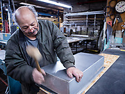 Sheetmetal worker Nestor Lugo using a rawhide mallet to fold the edge of a stainless steel bain-marie for a food cart. The interior has easily-cleaned radiused corners, and a folded-over lip to keep the hot water from sloshing out during transportation.