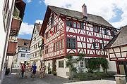 A family strolls by Haus Vetter, a half-timbered house on Bodenseeradweg in Stein am Rhein village, Schaffhausen Canton, Switzerland, Europe.