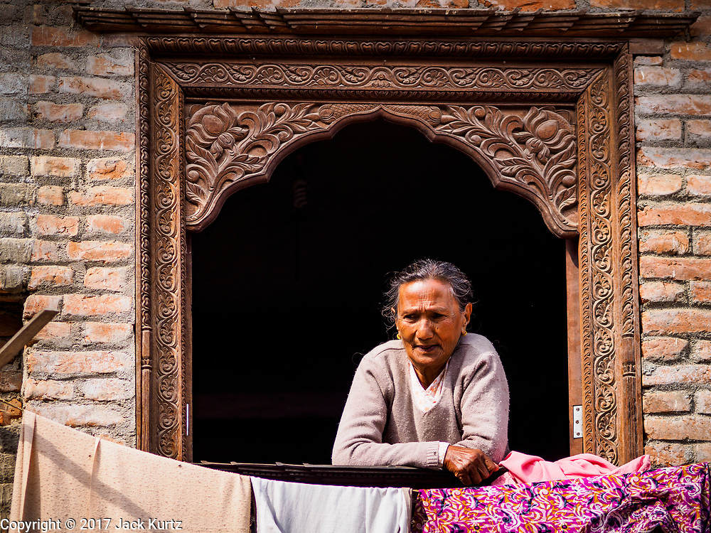 15 MARCH 2017 - BUNGAMATI, NEPAL: A woman on the balcony of her home in Bungamati. Bungamati, a community of wood carvers and artisans, used to be a stop on the tourist trail of the Kathmandu valley but since the 2015 earthquake few tourists visit the community. Recovery seems to have barely begun nearly two years after the earthquake of 25 April 2015 that devastated Nepal. In some villages in the Kathmandu valley workers are working by hand to remove ruble and dig out destroyed buildings. About 9,000 people were killed and another 22,000 injured by the earthquake. The epicenter of the earthquake was east of the Gorka district.            PHOTO BY JACK KURTZ