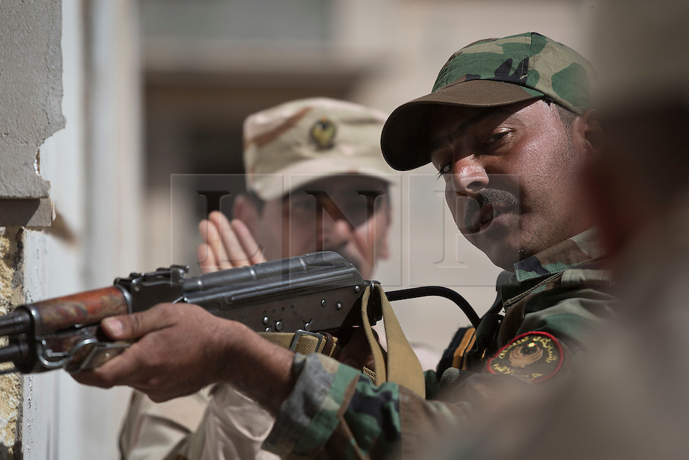 © Licensed to London News Pictures. 09/03/2015. Erbil, Iraq. A Kurdish peshmerga sergeant covers a door with his Kalashnikov rifle as he waits for a comrade to use a battering ram during an urban warfare training package, run by German soldiers, at a partially finished housing estate near Erbil, Iraq.<br /> <br /> The training is part of a four week platoon level infantry training package run by coalition forces aimed at improving the efficiency of the Iraqi Security Forces. Photo credit: Matt Cetti-Roberts/LNP