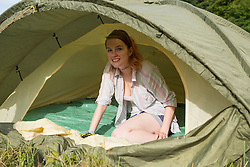 Portrait of a young woman sitting in tent and smiling, Bavaria, Germany
