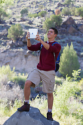 male hiker stopping to take a photograph with an iPad outdoors