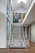 A view of the main entry stair, leading up to a photo by the photographer JR.