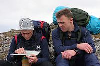 Tre menn med ryggsekker studerer kart og terreng, three men with backpacks study the map and terrain