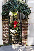 A wrought iron gate with a Christmas wreath at a historic home on Tradd Street in Charleston, SC.