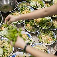 Preparing bowls of  bún thịt nướng in the kitchen of the popular restaurant Huyền Anh in Hue, Vietnam. Bún thịt nướng is a cold rice noodle dish topped with fresh herbs, vegetables, grilled pork and peanuts and served with a side of a sweet, vinegary, fish sauce-based dipping sauce infused with garlic and peppers.
