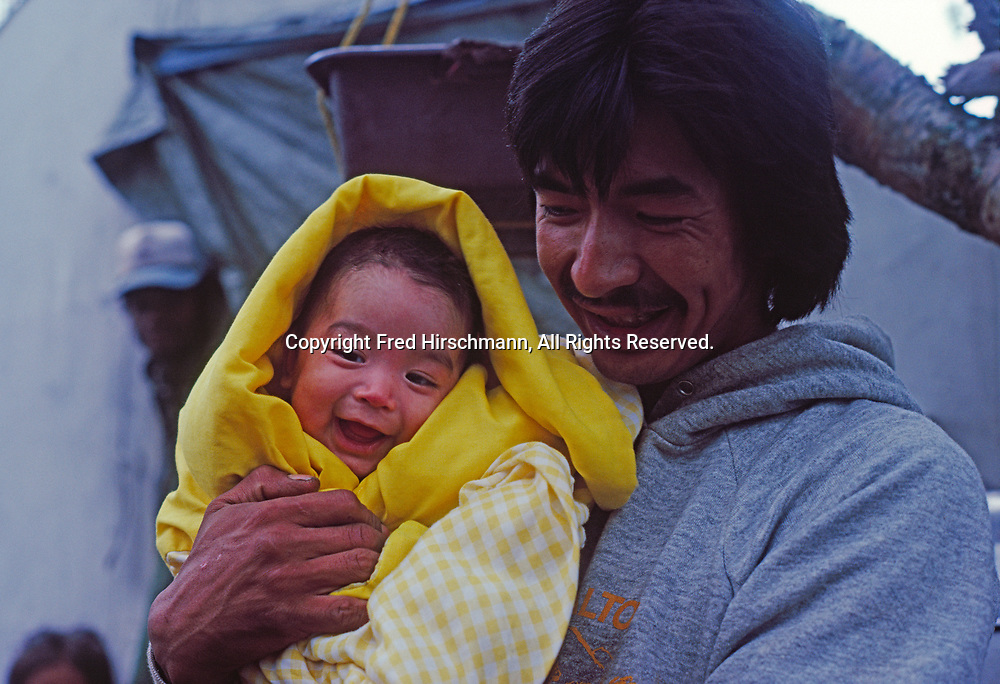 Ada Trefon with newborn baby, at Trefon family's subsistence fishing and berry picking camp on shore of Lake Clark northeast of Nondalton, Native Allotment within Lake Clark National Preserve, Alaska.