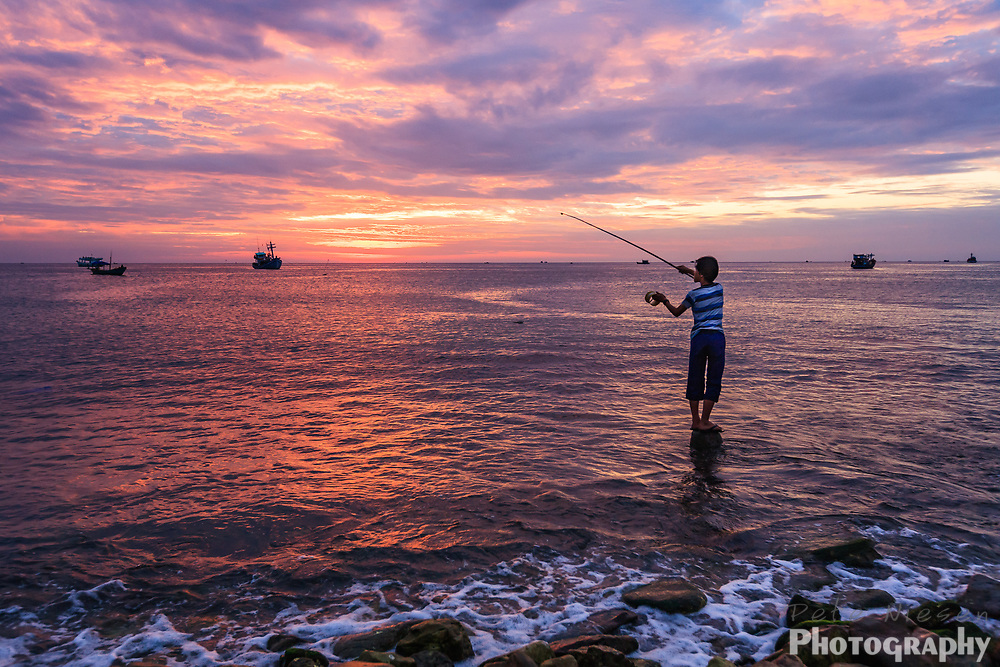 VIETNAM, PHU QUOC ISLAND: Vietnamese boy fishing  surrounded by the bright colors of sunset reflected in the ocean waters