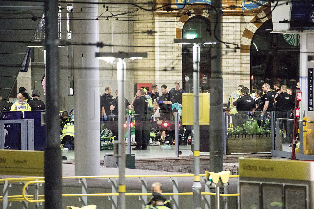 © Licensed to London News Pictures . FILE PICTURE DATED 23/05/2017 as Manchester prepares to mark a year since the Manchester Arena terror attack . Manchester, UK. Police and other emergency services tending to injured people on the platform at Victoria Station near the Manchester Arena after reports of an explosion. Police and other emergency services are seen near the Manchester Arena after Salman Abedi murdered 22 and injured dozens more at an Ariana Grande concert at Manchester Arena. Photo credit : Joel Goodman/LNP