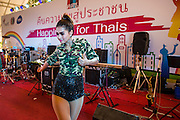 """15 JUNE 2014 - BANGKOK, THAILAND: A """"coyote dancer"""" performs during a """"Return Happiness to Thais"""" party in Lumpini Park in Bangkok. The Thai military junta, formally called the National Council for Peace and Order (NCPO), is sponsoring a series of events throughout Thailand to restore """"Happiness to Thais."""" The events feature live music, dancing girls, military and police choirs, health screenings and free food.   PHOTO BY JACK KURTZ"""