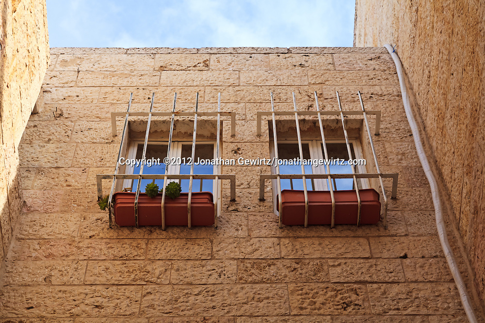 Two barred windows with planters in the stone wall of a house in the Jewish Quarter of the Old City of Jerusalem. WATERMARKS WILL NOT APPEAR ON PRINTS OR LICENSED IMAGES.