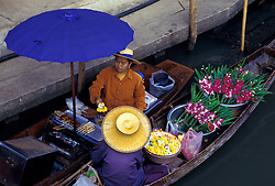 Asia, Thailand, 104 km southwest of Bangkok. Damnoen Saduak Floating Market. Woman buys flowers while cooking on canoe under large umbrella
