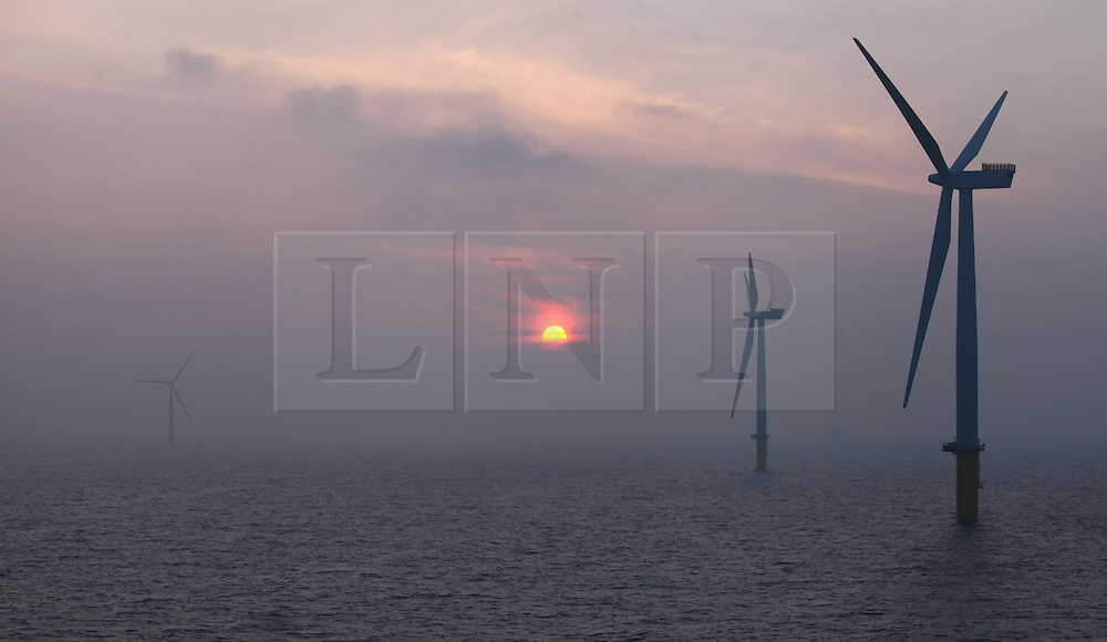 © Licensed to London News Pictures. 26/03/2014. North Wales, UK. The sun rising over the Gwynt y Môr Offshore Wind Farm off the coast of North Wales this morning, 26th March 2014. Photo credit : Rob Arnold/LNP