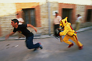 The masked El Colacho, the devil incarnate, chases the troublesome village youngsters, trying to hit them with his whip, during the Fiesta del Colacho, in Castrillo de Murcia, Burgos province, Spain. The Fiesta del Colacho is held every year at the time of the Catholic feast Corpus Christi.