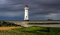 A container ship sails out of the River Mersey past New Brighton lighthouse.