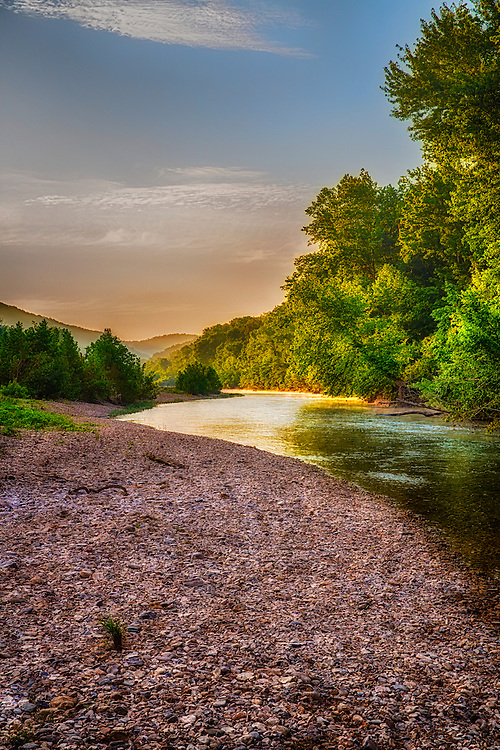 The warmth and light of the morning sun peeks over from the horizon along Buffalo River