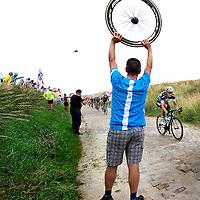 Frankrijk, Cambrai-07-2015.<br /> Wielrennen, Tour de France.<br /> Etappe van Seraing naar Cambrai<br /> Tony Martin, de latere winnaar, op kasseienstrook nr 5. De mechanicien van Sky houdt een wiel omhoog voor het geval Froome of iemand anders van de Sky ploeg lek zou rijden op de kasseien.<br /> Foto: Klaas Jan van der Weij
