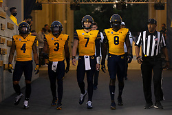 California game camptains Nikko Remigio (4), Elijah Hicks (3), Chase Garbers (7) and Kuony Deng (8) emerge from the tunnel before an NCAA college football game Nevada, Saturday, Sept. 4, 2021, in Berkeley, Calif. The official is field judge Michael Hall. (AP Photo/D. Ross Cameron)