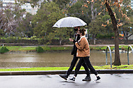 A young couple sheltering under an umbrella walk along the Yarra as rain falls on Melbourne during COVID-19 in Melbourne, Australia. Victoria has recorded 14 COVID related deaths including a 20 year old, marking the youngest to die from Coronavirus in Australia, and an additional 372 new cases overnight. (Photo by Dave Hewison/Speed Media)