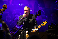 """© Licensed to London News Pictures . 05/02/2016 . Manchester , UK . PETER HOOK . """" Hacienda Classical """" debut at the Bridgewater Hall . The 70 piece Manchester Camerata and performers including New Order's Peter Hook , Shaun Ryder , Rowetta Idah , Bez and Hacienda DJs Graeme Park and Mike Pickering mixing live compositions . Photo credit : Joel Goodman/LNP"""