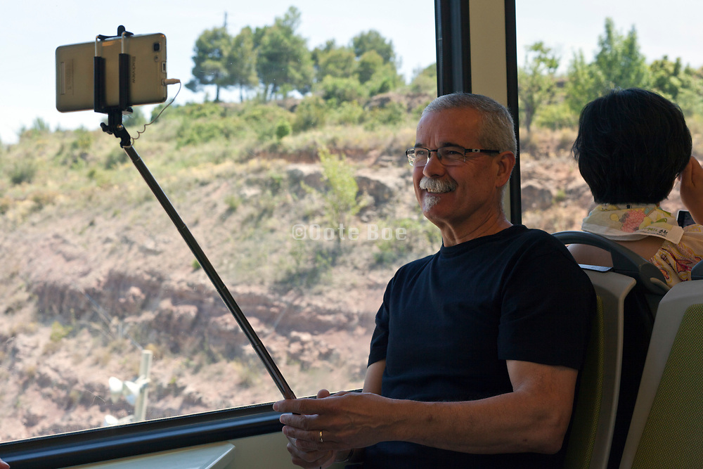 person making a selvie with mobile phone while traveling by public transportation to Montserrat Spain