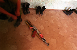 An AK-47 lay  the ground while the soldier laces his boots up
