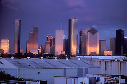 Western end of downtown Houston at dusk with sunset reflecting in the buildings.