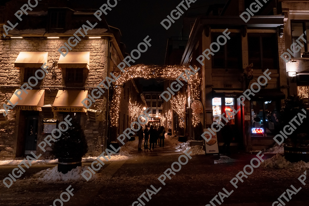 Montreal, Quebec, Canada - January 3, 2021 Rue Saint Amable during winter night with christmas lights and snow with unrecognizable people viewed from Place Jacques-Cartier in Montreal Old Port