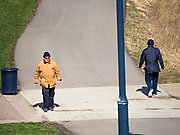 """29 MARCH 2020 - DES MOINES, IOWA: People social distance while they walk on a paved trail near downtown Des Moines. On Sunday morning, 29 March, Iowa reported 336 confirmed cases of the Novel Coronavirus (SARS-CoV-2) and COVID-19. There have been four deaths attributed to COVID-19 in Iowa. Restaurants, bars, movie theaters, places that draw crowds are closed until 07 April. The Governor has not ordered """"shelter in place""""  but several Mayors, including the Mayor of Des Moines, have asked residents to stay in their homes for all but the essential needs. People are being encouraged to practice """"social distancing"""" and many businesses are requiring or encouraging employees to telecommute.         PHOTO BY JACK KURTZ"""