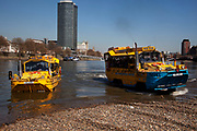 Scene along the River Thames as two Duwk amphibious vehicles drive out of the river onto dry land. The Duck Tours company. London