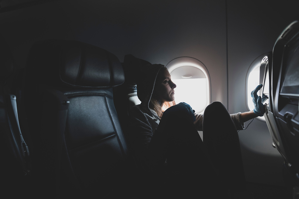 In Flight - March 21, 2020: Erin Guiney, a passenger on a mostly empty Delta Airlines flight 2937 from New York LaGuardia to Atlanta, uses a latex glove to navigate the seat-back entertainment screen during the COVID-19 pandemic.