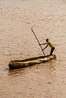 Dassanach tribe man rowing a dugout canoe called a tankua across the Omo River,, Omo Valley, Ethiopia.