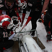 New Canaan players warm themselves on the sideline during the New Canaan Rams Vs Darien Blue Wave, CIAC Football Championship Class L Final at Boyle Stadium, Stamford. The New Canaan Rams won the match in snowy conditions 44-12. Stamford,  Connecticut, USA. 14th December 2013. Photo Tim Clayton