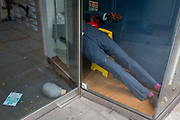 After months of a menswear retailers forced closure during the UK Coronavirus pandemc lockdown, one of its mannequins has fallen over on to the shop floor, its head lying by the door. The number of deaths from Coronavirus in the last 24hrs has increased by 287 to 37,979 while the government lowered the national Covid-19 alert level from 4 to 3, meaning the virus is considered to be in general circulation .. with a gradual reduction in restrictions, on 19th June 2020, in the City of London, England.