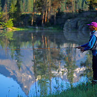 A man fishes in a pond in the Absaroka-Beartooth Mountains of Wyoming.  Reflected in the water is Pilot Peak, a landmark of the region.