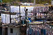 Traditional Indian professional hand laundry, Dhobi Ghat, and laundryman hanging clothes to dry in Mahalaxmi, Mumbai, India