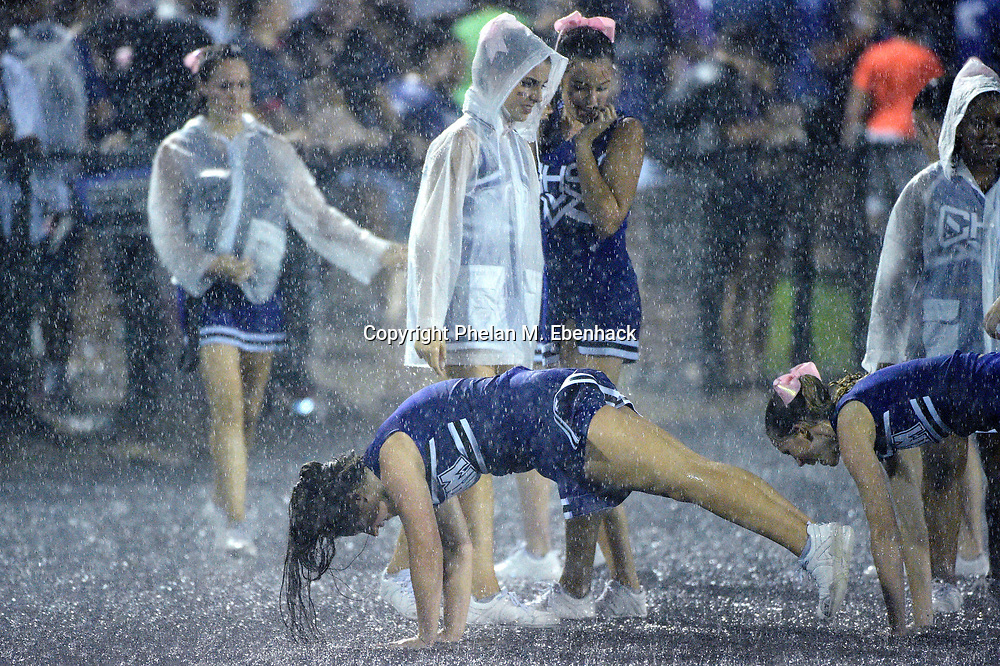 The Celebration cheerleaders perform in the rain during the second half of a high school football game against Saint Cloud in Celebration, Fla., Friday, Oct. 2, 2015. (Photo by Phelan M. Ebenhack)
