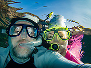 """Snorkelers: man & woman selfie in rippled water. We kayaked on a Kona Boys tour to the Captain Cook Monument in Kealakekua Bay State Historical Park starting from Napoopoo Pier, on the Kona Coast of the Big Island, Hawaii, USA. With one of the most pristine coral reefs for snorkeling in the state, Kealakekua Bay is protected as a State Marine Life Conservation District (MLCD). British Captain James Cook was the first European to reach the Hawaiian islands (in January 1778 at Waimea harbour on Kauai), and he named the archipelago the """"Sandwich Islands."""" During his second voyage to the Hawaiian Islands, Captain Cook arrived at Kealakekua Bay in 1779. Thought by the natives to be a god, due to his arrival during a celebration and time of peace for Lono, Cook was treated royally. But the following month he was killed in a skirmish on the shores of Ka'awaloa Cove following a series of incidents between his crew and the Hawaiians. In 1874, the 27-foot monument was erected nearby in Cook's honor by his countrymen. On the lava flats behind Cook Monument are the ruins of the ancient village of Ka'awaloa. For this photo's licensing options, please inquire."""
