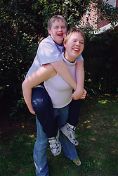 Teenage girl giving brother with Downs Syndrome piggy back in garden,