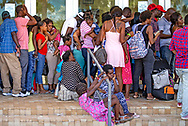 People wait to be processed and checked in to a shelter in Nassau, Bahamas, for victims of Hurricane Dorian on Monday, September 9, 2019.