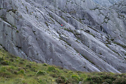 Rock climbers scale a steep rock-face in the mountains surrounding  Llyn Idwal in the Cwm Idwal National Nature Reserve on 17th September 2020 in Pont Pen-y-benglog, Snowdonia, Wales, United Kingdom. Llyn Idwal is a small lake that lies within Cwm Idwal in the Glyderau mountains of Snowdonia. It is named after Prince Idwal Foel, a grandson of Rhodri Mawr, one of the ancient Kings of Wales.