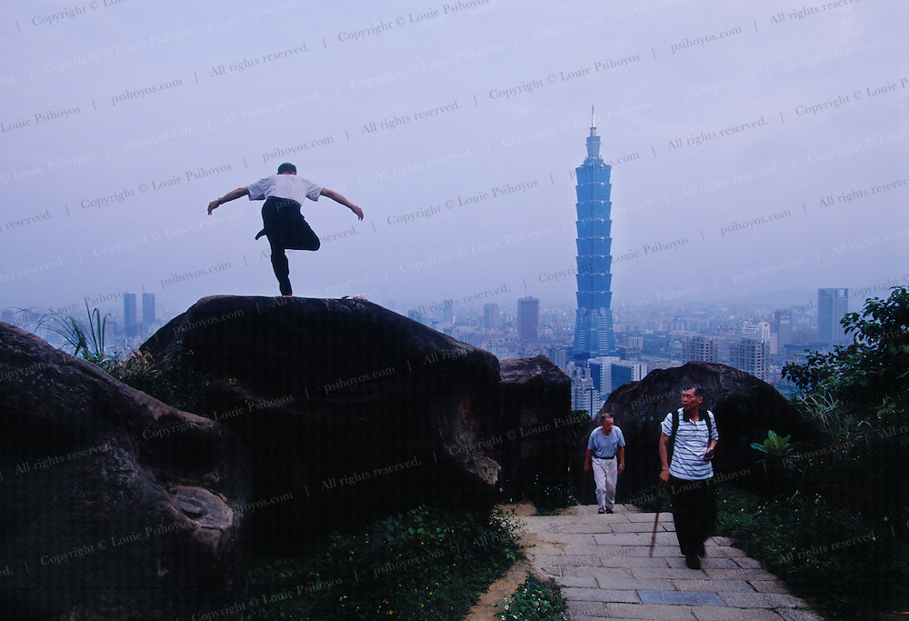 A practitioner of Tai Chi does a morning workout on a rock on Elephant Mountain above Taipei.  Tai Chi is a common mental and physical art that is openly seen around the city beginning around sunrise.  The man's workout is so common that it would not even draw stares from local hikers.