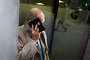 The cover of a smartphone obscures the face of a businessman in the City of London. Holding his handset to his ear, it hides his features making him another anonymous person going about his business in the capital.