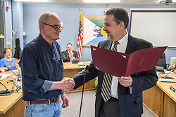 Laconia Daily Sun reporter Michael Kitch is congratulated by  Laconia Mayor Ed Engler following the reading of a proclamation marking Kitch's 14 years of covering the Laconia city council on Monday, April 24, 2017.  (Alan MacRae for the Laconia Daily Sun)