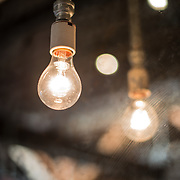A bare lightbulb is reflected in a weathered vintage mirror.