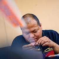 070514       Cable Hoover<br /> <br /> Bead artist Lionel Yazzie uses a needle and thread to lace small beads onto his loom during an indoor arts market at the Hozho Center in Gallup Saturday.