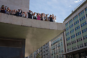 Portuguese office workers have left their desks and PCs to climb on to a buildings ledge to watch their national football team during their victory procession through the capitals streets, the day after the Euro 2016 final with France, on 11th July 2016, in Lisbon, Portugal. Lined up along the concrete ledge near Praca Marques de Pombal in the largely corporate and banking district of the city, they take photos and cheer their favourite players, including the national hero/deity, Christiano Ronaldo.