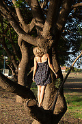 Young blonde woman is protecting a tree Woman