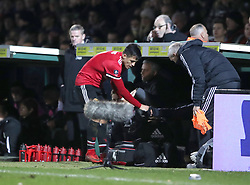 Manchester United's Alexis Sanchez in the dugout as Manchester United manager Jose Mourinho (back) looks on during the Emirates FA Cup, fourth round match at Huish Park, Yeovil.