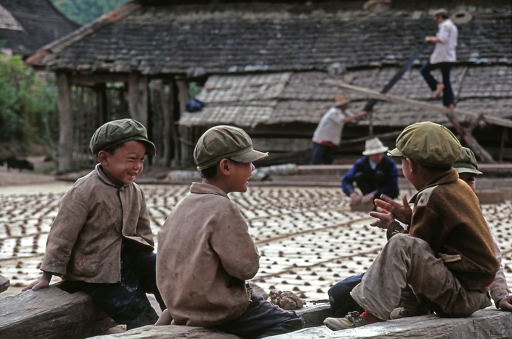 In the middle of a bamboo forest, at the border of Laos, children are laughing while playing with mud, beside a field of bricks drying under the sun. Xichuangbanna, China.